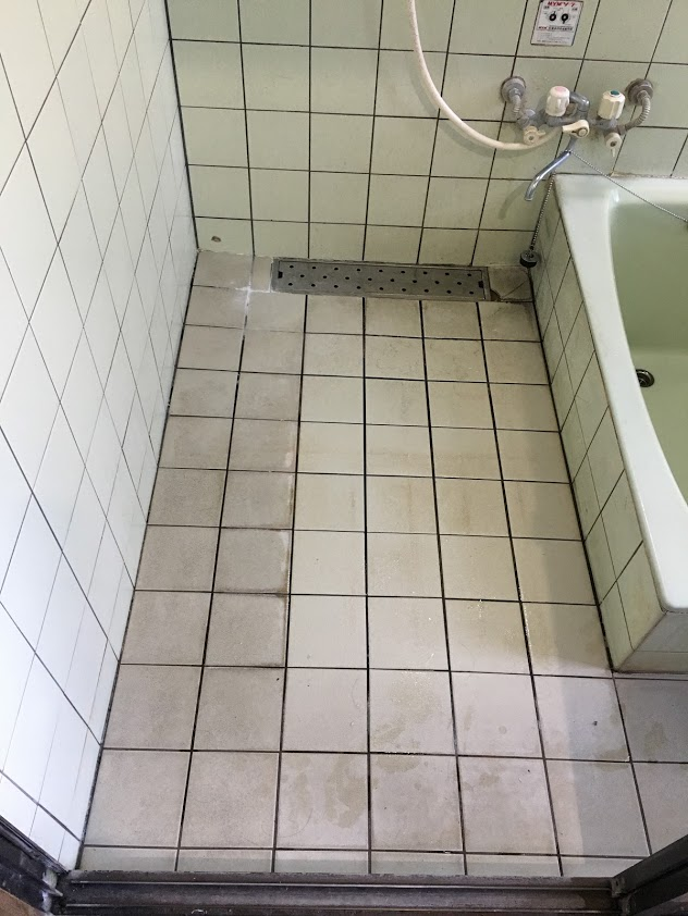 クリーニング前の白いタイルの浴室